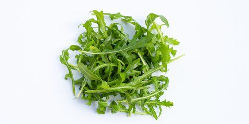 Fresh green rocket salad on white background.